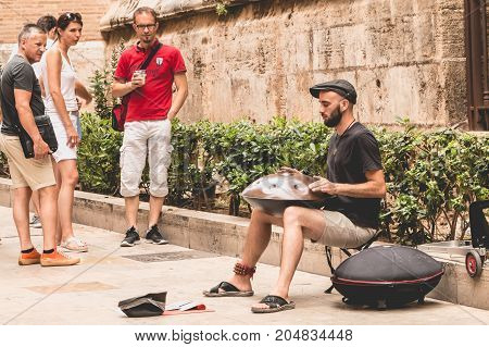 VANLENCIA SPAIN - june 16 2017: musician plays hang drum in the street and passers-by stops to listen
