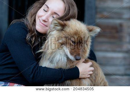 A beautiful woman and her dog nenets shepherd laika sitting near house. Friendship between man and dog. Hygge style photo