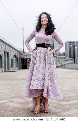 portrait of beautiful female in luxury pink dress standing in the city center