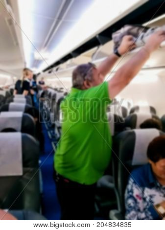 Blured view of interior of airplane with passengers on seats