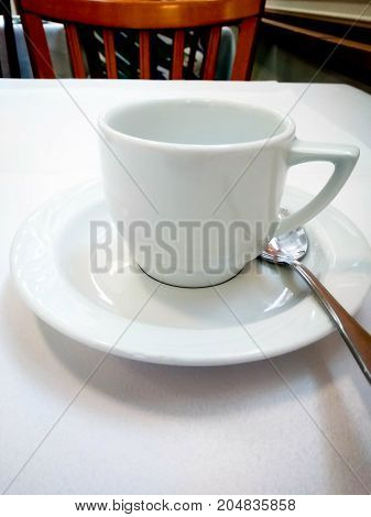 White empty coffee porcelain cup and saucer stands on a table with a white tablecloth