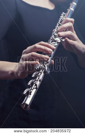Close-up of a woman playing the flute. Studio shot