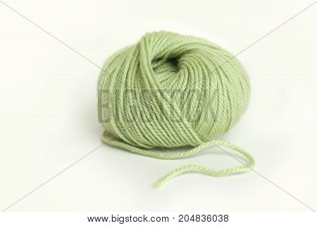 a skein of green wool yarn on white background