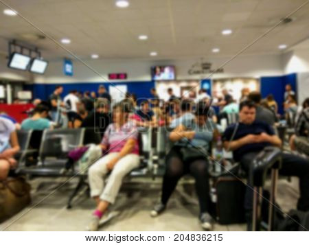 Blured view of passengers are waiting in a crowded space near the gates for the delayed flight