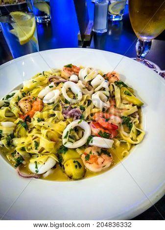 Healthy whole grain pasta with shrimpscalamari and herbs . Restaurant menu photo