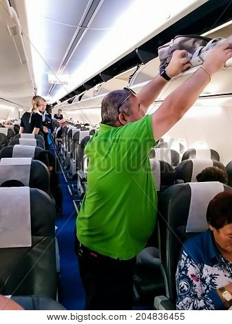TEL AVIV ISRAEL - JULY 11 2017: Interior of modern commercial airplane with passengers on their seats waiting to taik off.
