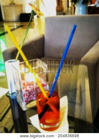 Blurred view of alcoholic cocktail with ice two plastic straws