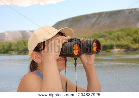 The woman is looking through binoculars standing near the river. Holds binoculars with both hands