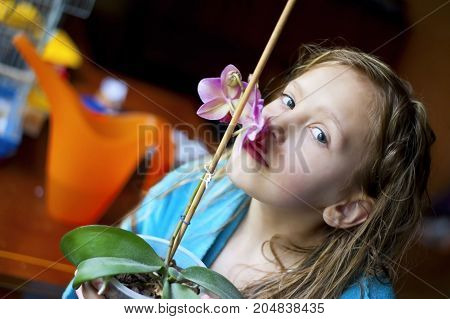 Girl sniffing beautiful orchids. The girl has wet hair because recently took a bath. She is dressed in a bathrobe