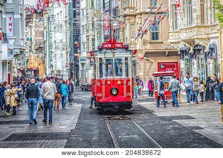 ISTANBUL, TURKEY: Istiklal street and famous red tram going along the street on October 6, 2014. Istiklal is a most popular shopping and entertainment place in Istanbul