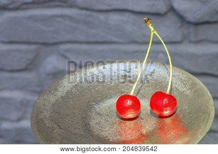 Two red cherries with cuttings on an iron plate