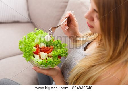 Young pregnant woman eating green salad closeup. Unrecognizable expectant blonde sitting on sofa and having fresh snack. Healthy nutrition and pregnancy concept