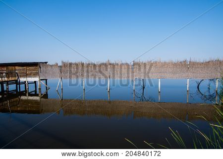 photograph of a fence over water with its own symmetrical reflections