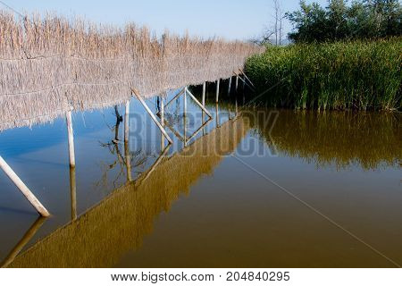 photograph of a fence over the river with its reflections in the water