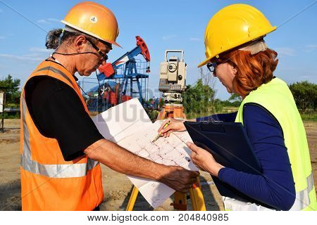 Two surveyors at work on an eastern Europe oil well with crude oil pumpjack in background