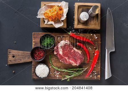 Raw rib eye steak with herbs. Fresh meat with chilli on wooden desk. Russian korean salad and salt in wooden boxes, top view.