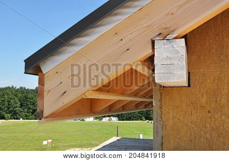 Repair and installing house roof eaves, soffits and fascia boards with attic insulation.