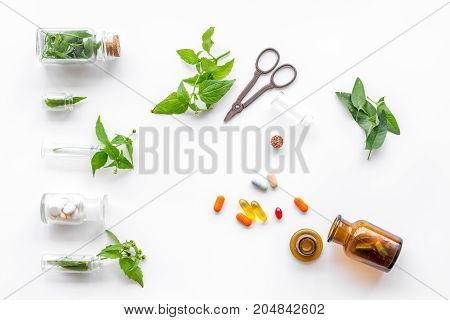 Herbal medicine. Leaves, bottles, pills and sciccors on white background top view.