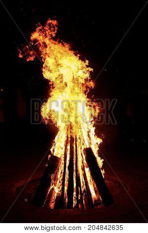 Big high yellow bonfire on black backgrounde at night