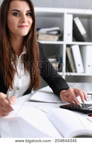 Businesswoman In The Office Keeps Her Hand On The Calculator