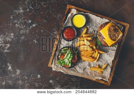 Take away burger menu on wooden tray top view. Black bun cheeseburger with baked potato wedges and sauces set, fast food concept