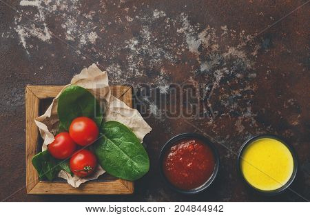Tomatoes and basil leaves in wooden frame with red and yellow sauces on kitchen table, top view, copy space