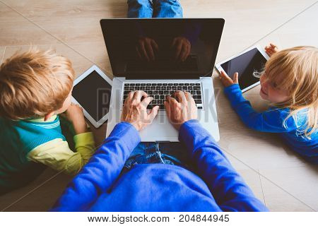 father with kids using laptop and tablet, modern technology at home