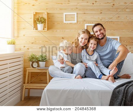 happy family mother father and children daughter and son in bed bedroom