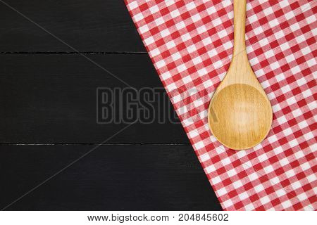 Wooden spoon over plaid tartan tablecloth on black wooden table in top view