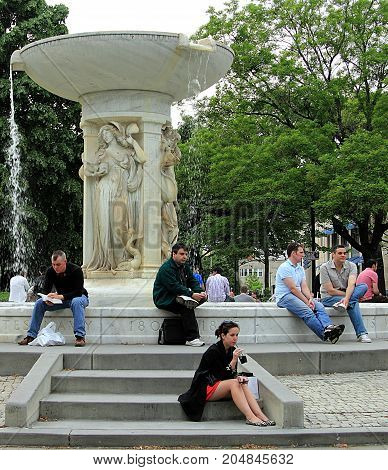 Washington DC - April 30. 2011: People relaxing in front of Daniel Chester French's marble fountain in the center of Dupont Circle
