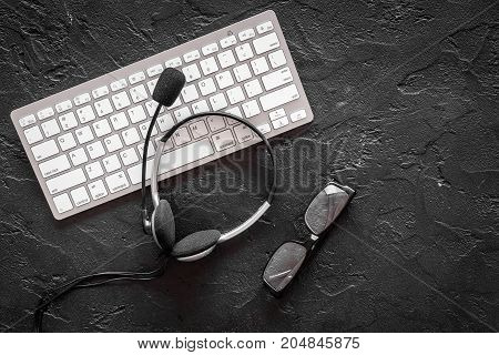 Call center manager's workplace. Headphones near keyboard on black background top view.