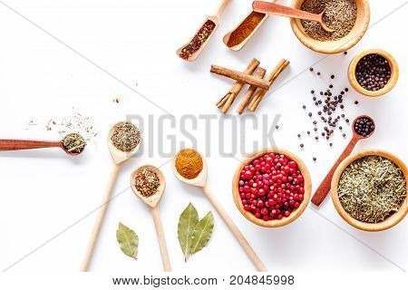 Colorful dry herbs and spices for cooking food on white kitchen table background top view space for text