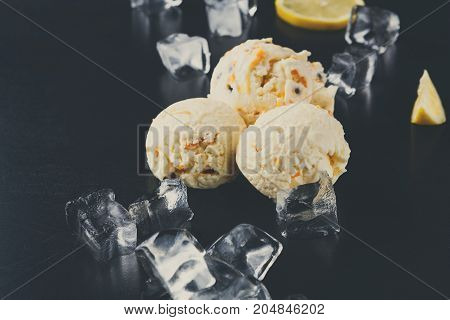 Ice cream scoops with ice cubes and lemon slices on black background. Delicious cold sweet dessert, copy space