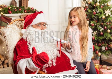 Here are my wishes. Pretty girl is sitting on Father Frost knees and giving him the list of wishes. Old man is looking at paper with shock