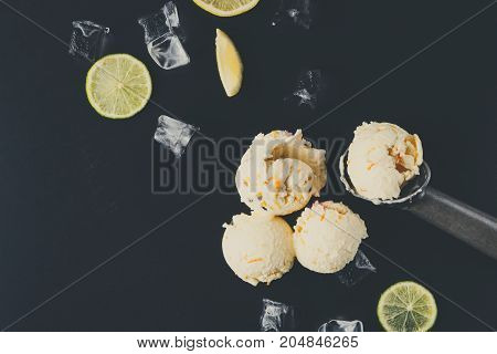 Ice cream scoops with ice cubes and lemon slices and scoop on black background. Delicious cold sweet dessert, copy space