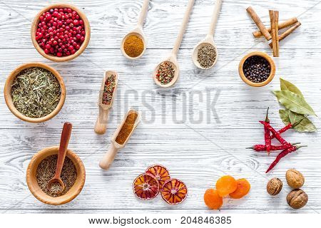 Variety of spices and dry herbs in ceramic bowls on wooden kitchen table background top view pattern