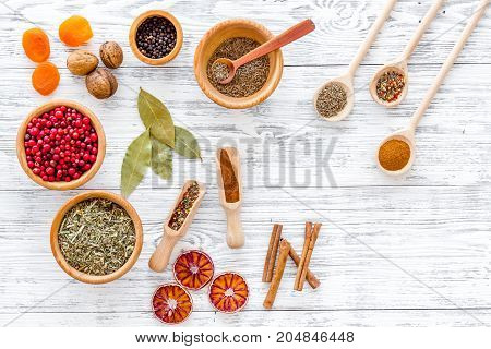 Colorful dry herbs and spices for cooking food on light wooden kitchen table background top view