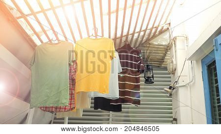 Hang the clothes are t-shirt hanging on the roof batten under the sun in my house.