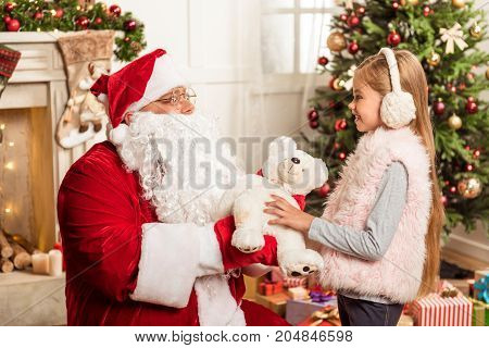 This present is for you. Kind senior bearded man in red and white costume is giving teddy bear to child. Girl is standing near Christmas tree and laughing