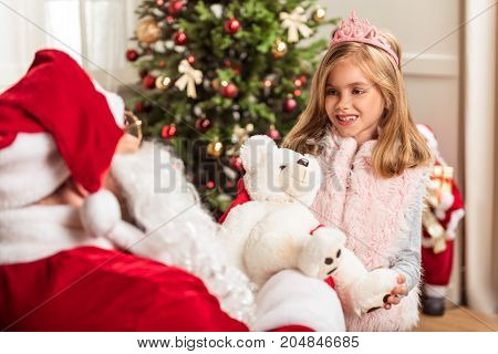Happy little princess is getting gift from Santa Claus. She is standing and smiling gratefully. Portrait
