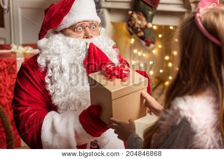 You deserve this present. Portrait of excited Santa Claus giving box to female child. He is sitting on comfortable armchair in red costume