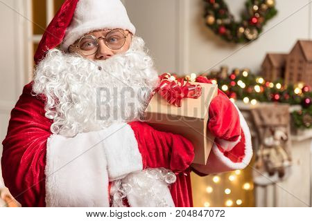 Merry Christmas. Portrait of kind Father Frost showing present box and smiling. He is wearing red and white costume