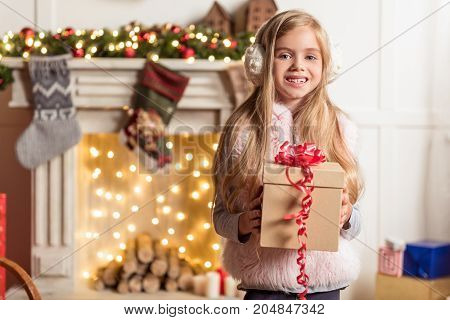 What is inside. Portrait of curious little girl holding Christmas present box and smiling. Copy space in left side