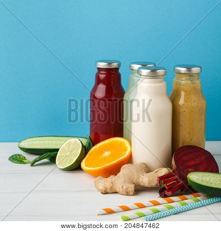 Healthy food. Assortment of fruit and vegetables detox smoothies with ingredients in glass bottles on pastel blue wall background, copy space.