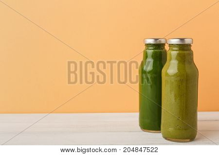 Healthy food. Assortment of fruit and vegetables detox smoothies in glass bottles on pastel orange wall background, copy space.