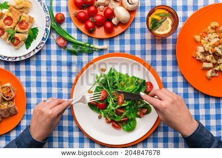Unrecognizable woman eating fresh salad with greens and tomatoes on checkered tablecloth background. Healthy eating concept, organic vegetables top view.
