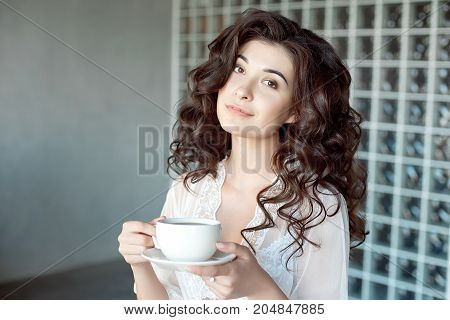 Attractive girl enjoying a cup of coffee in a white transparent peignoir. Model with medium-brown curly hair and nice body. Close-up portrait.
