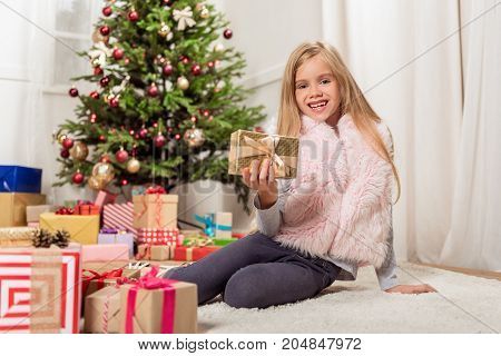 I like Christmas. Portrait of happy girl showing wrapped gift box to camera and smiling. She is sitting on floor near lots of boxes with fir-tree on background
