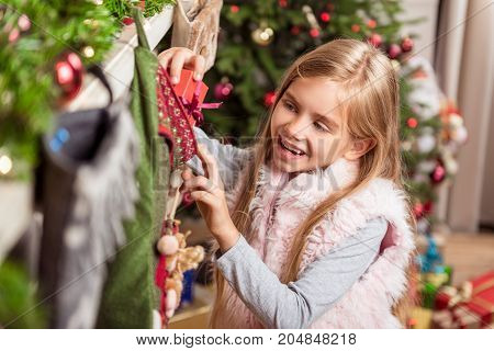 Portrait of excited girl putting small present box inside the Christmas sock. She is standing near fireplace and laughing