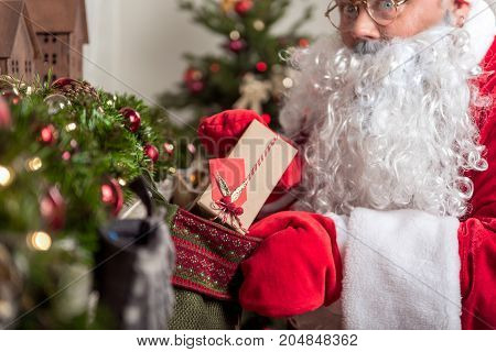 Mysterious Santa Claus is putting gift box inside big sock near fireplace. Focus on wrapped box with ribbon